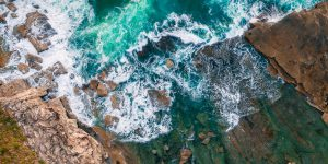Aerial shot of the water and rocks on the coast