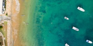 Aerial shot of the water showing beach, boats and kayaks