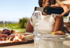 Two people enjoying cheese platter and glass of wine at a table together