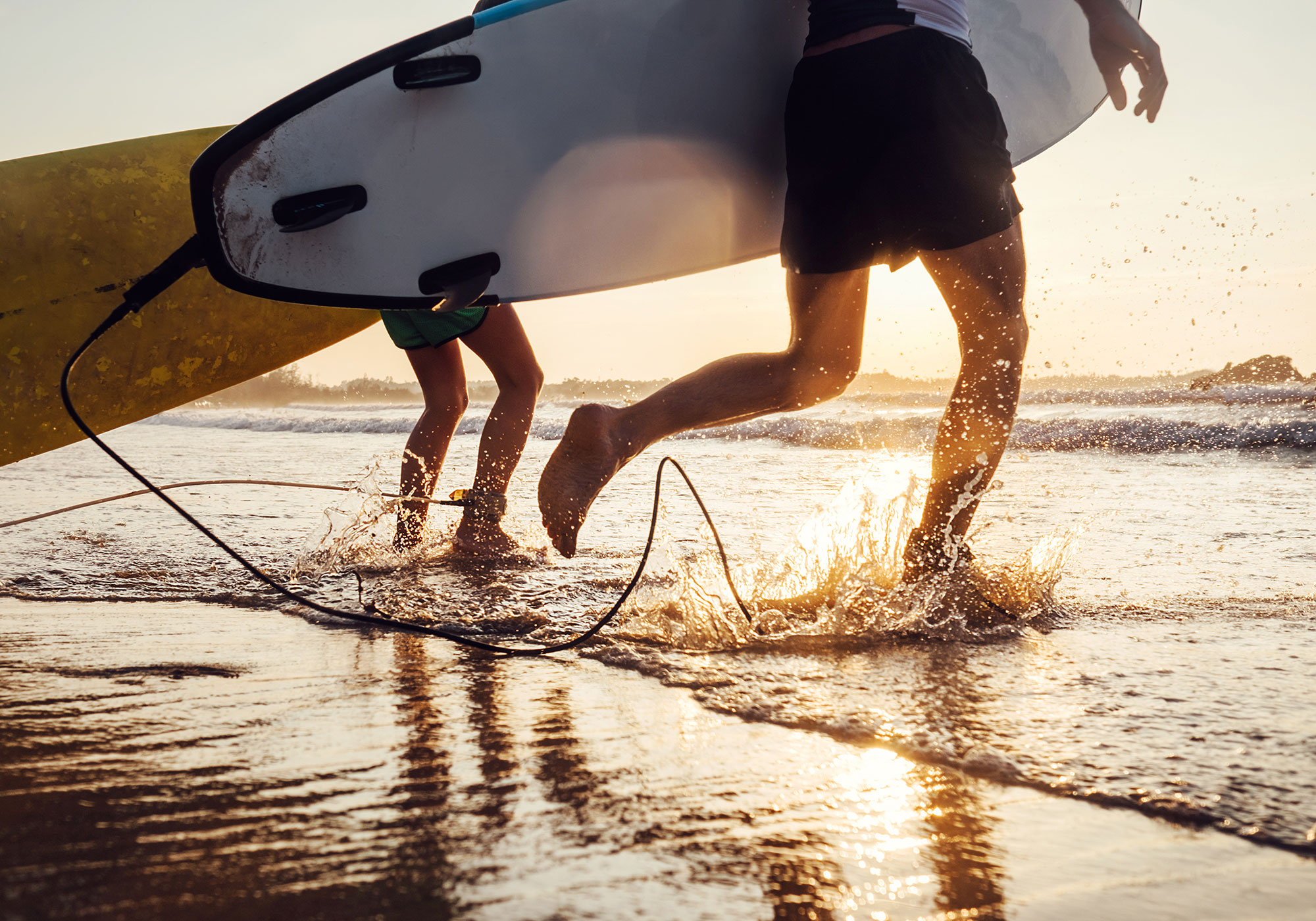 Shallow water at the beach with two men running into the water with surfboards