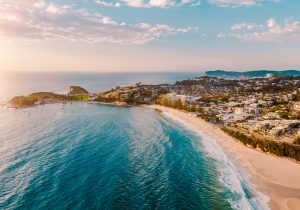Rolling blue waves and pristine beach alongside town of Terrigal